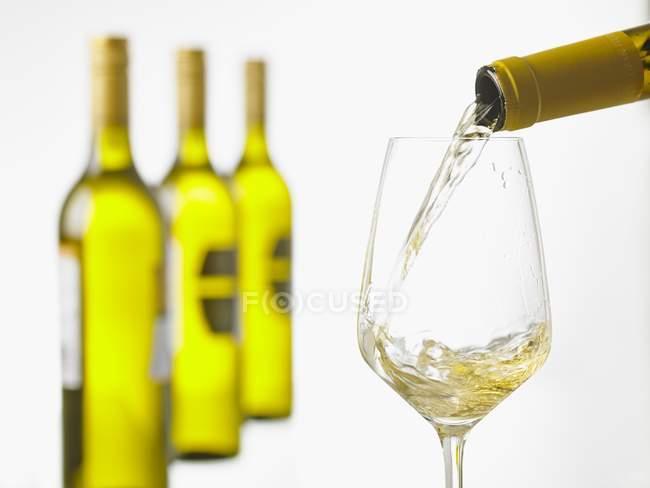 Белый, выливают в стакан — стоковое фото