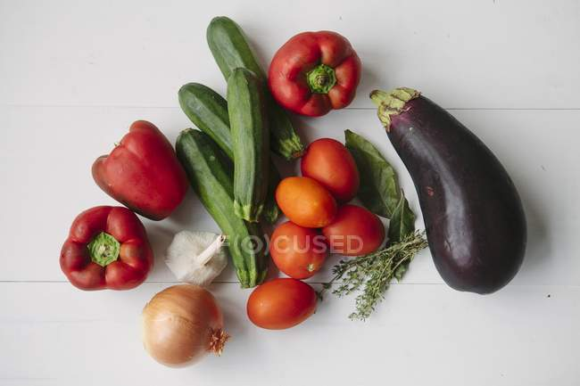Vegetables and herbs for ratatouille on white wooden surface — Stock Photo