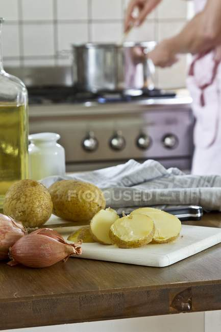 New potatoes and shallots in a kitchen and blurred man on background — Stock Photo