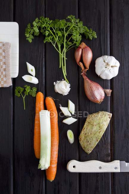 An arrangement of soup vegetables and parsley on dark wooden surface — Stock Photo