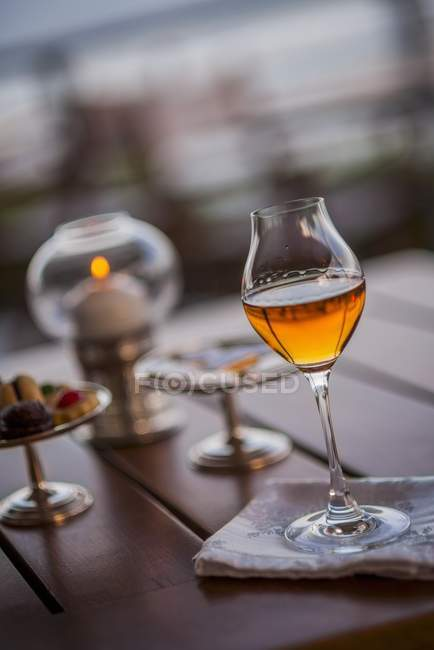 Closeup view of liqueur in tulip glass on table outdoors — Stock Photo
