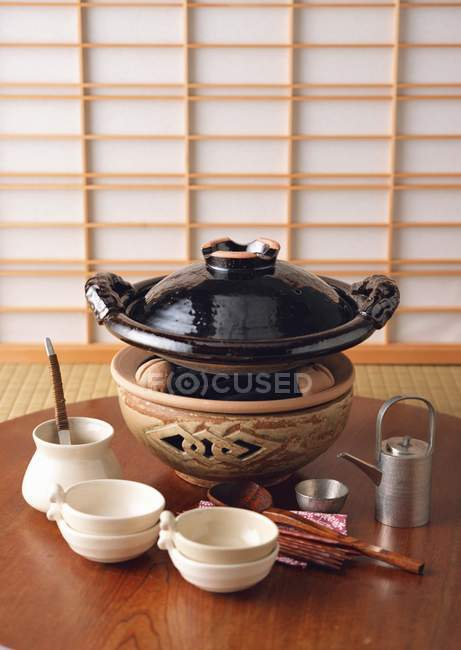 Closeup view of Japanese stew dish on coal with crockery on wooden table — Stock Photo