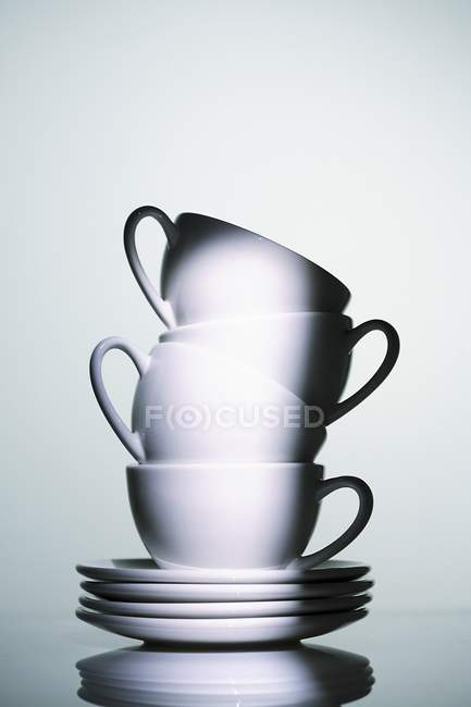 Closeup view of stacked white cups and saucers — Stock Photo