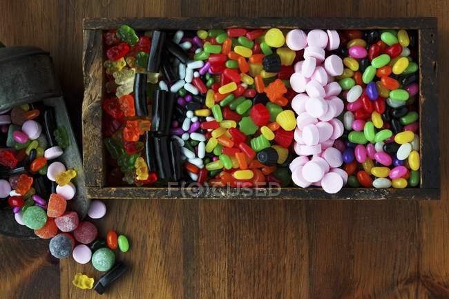 Vista dall'alto di vari dolci colorati in scatola di legno — Foto stock