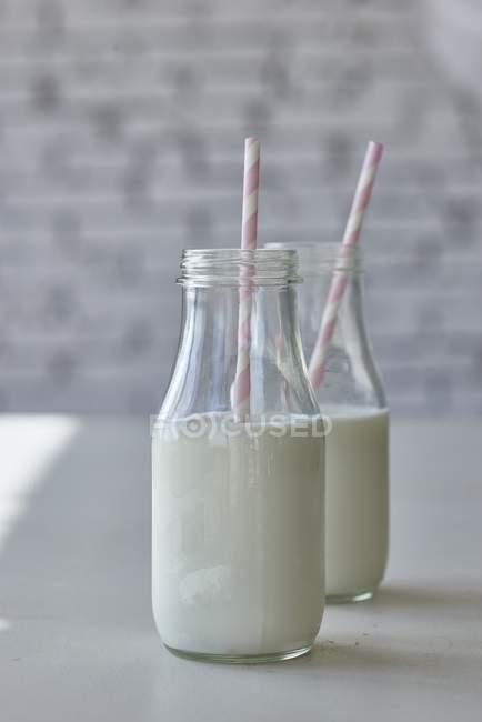 Flaschen Milch mit Strohhalmen — Stockfoto