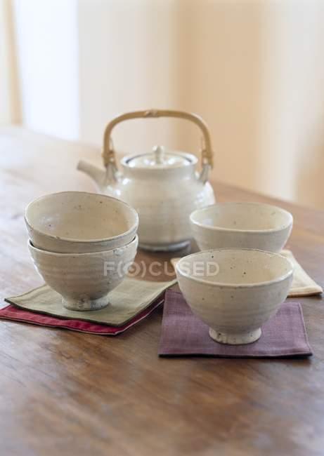 Vista elevada tigelas e bule com guardanapos na mesa de madeira — Fotografia de Stock