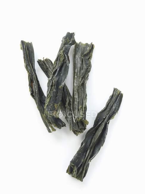 Closeup Draufsicht des getrockneten Wakame Algen auf weiße Fläche — Stockfoto