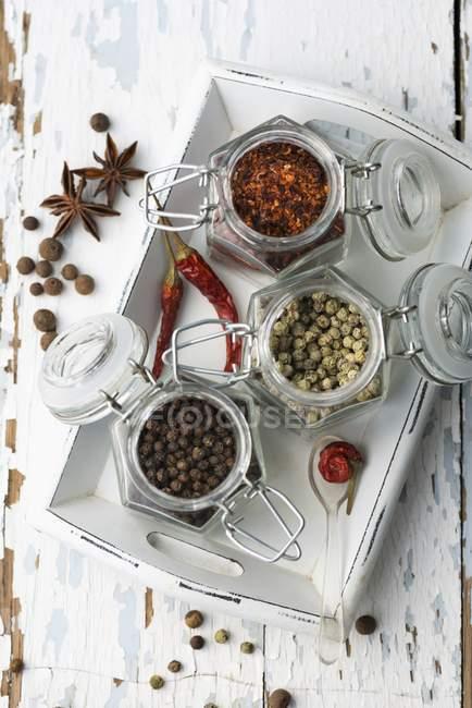 Diverses épices dans des bocaux de stockage sur un plateau en bois — Photo de stock