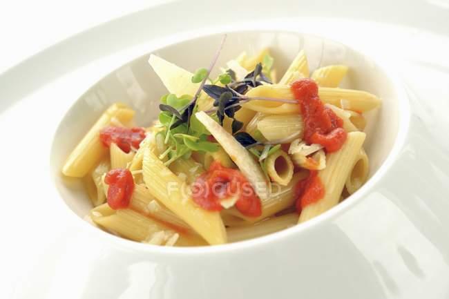Pasta Penne con ketchup, queso y hierbas - foto de stock