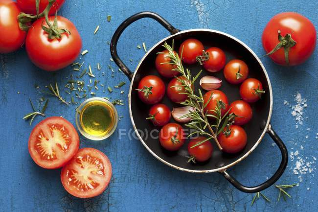 Cherry tomatoes with rosemary and olive oil — Stock Photo