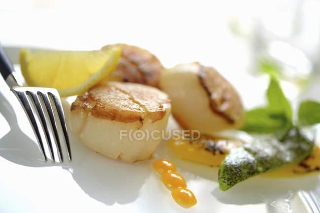 Capesante fritte con verdure su piatto bianco con forchetta — Foto stock