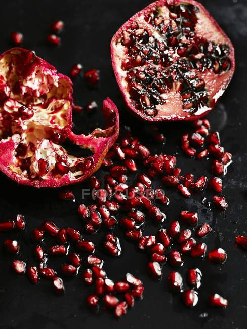 Halved pomegranate and seeds — Stock Photo