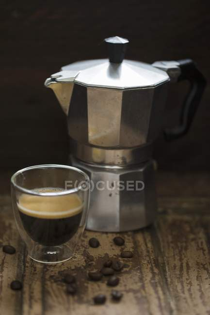 Coffee maker and glass of espresso — Stock Photo