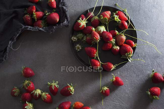 Fresh strawberries with plate and fabric — Stock Photo