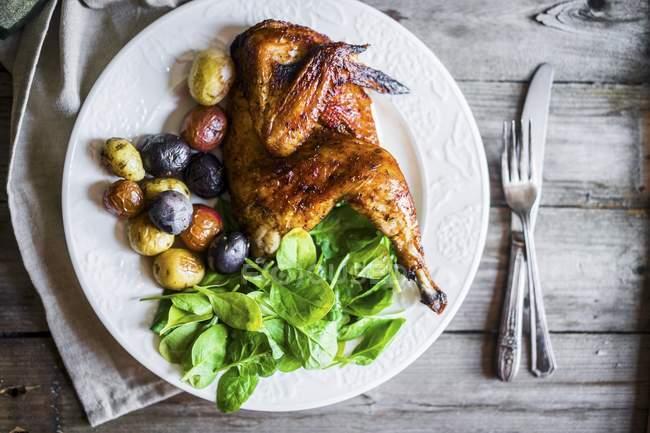 Meio frango grelhado com batatas assadas — Fotografia de Stock