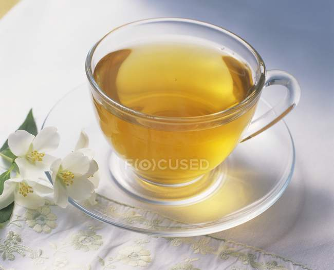 Cup of green tea with jasmine flowers — Stock Photo