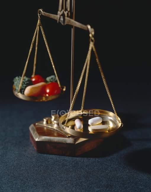Nahrungsergänzungsmittel und Gemüse auf einer Waage auf schwarzem Hintergrund — Stockfoto