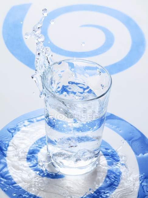 Water splashing into a glass — Stock Photo