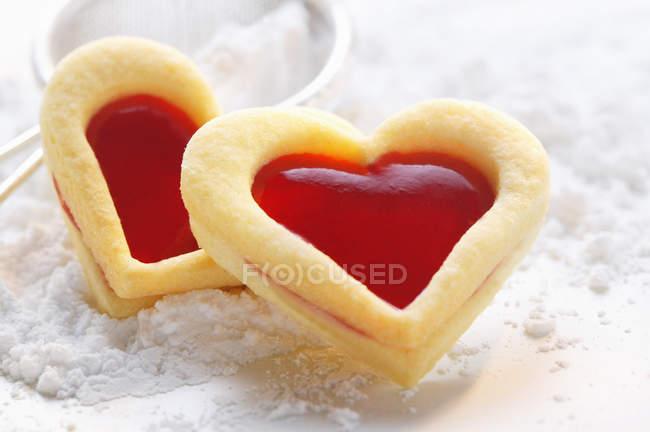 Vue des coeurs de pâte sucrée avec framboise confiture sur le sucre à glacer — Photo de stock