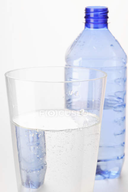 Closeup view of mineral water in glass in front of plastic bottle — Stock Photo