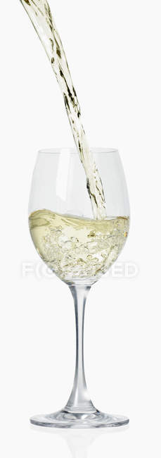 Pouring white wine into glass — Stock Photo