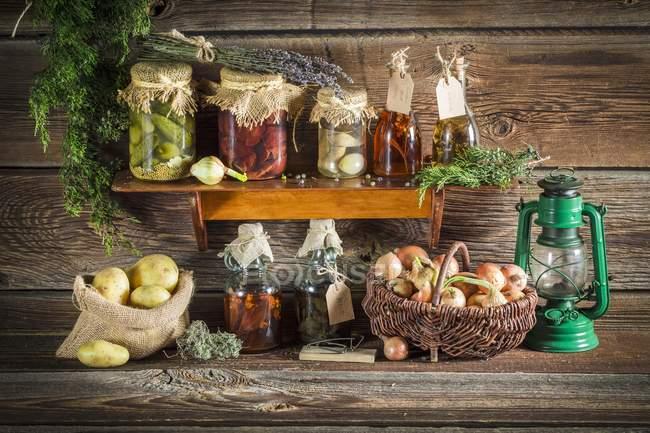 Различные сохранившиеся овощи и грибы на деревянной полке — стоковое фото