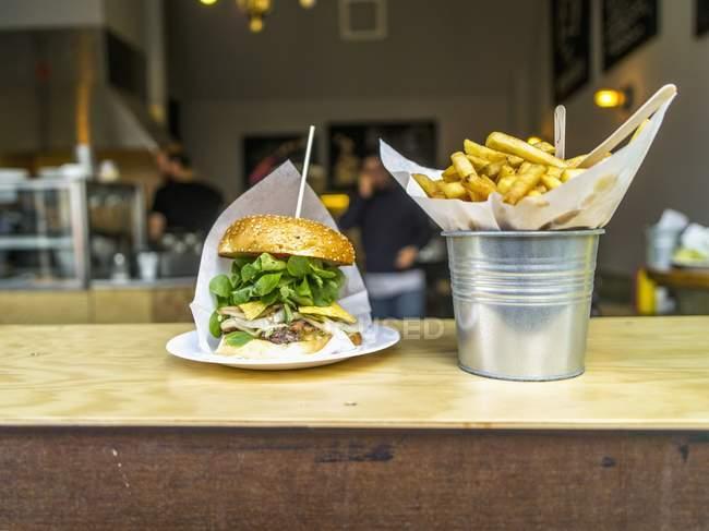 Hamburger sur plaque et chips — Photo de stock