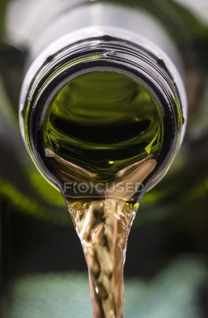 Лить белое вино из бутылки — стоковое фото