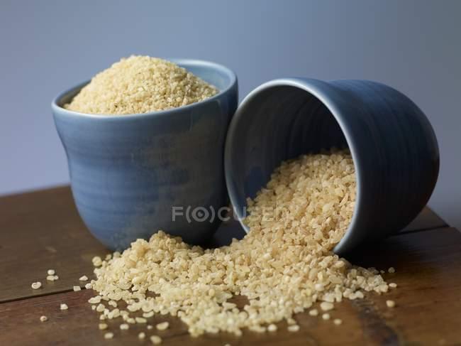 Bulgur y cuscús en tazones azules - foto de stock