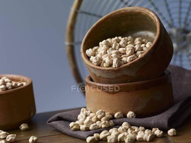 Kichererbsen in einer Steingutschüssel über der Holzoberfläche — Stockfoto
