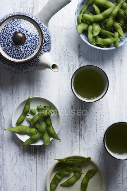 Edamame закуски подаються з чаєм над деревної поверхні — стокове фото