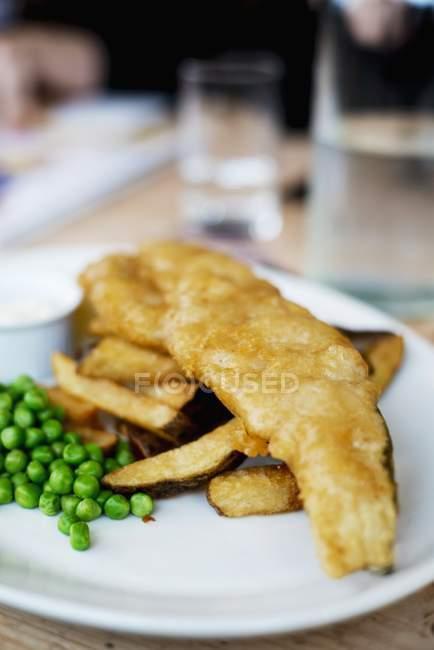 Fish and chips avec pois sur plaque blanche — Photo de stock