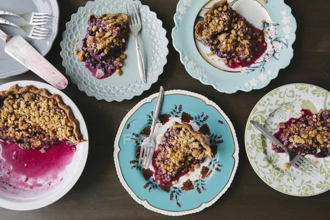 Вид зверху чорничний пиріг порцій на тарілки з вилами — стокове фото