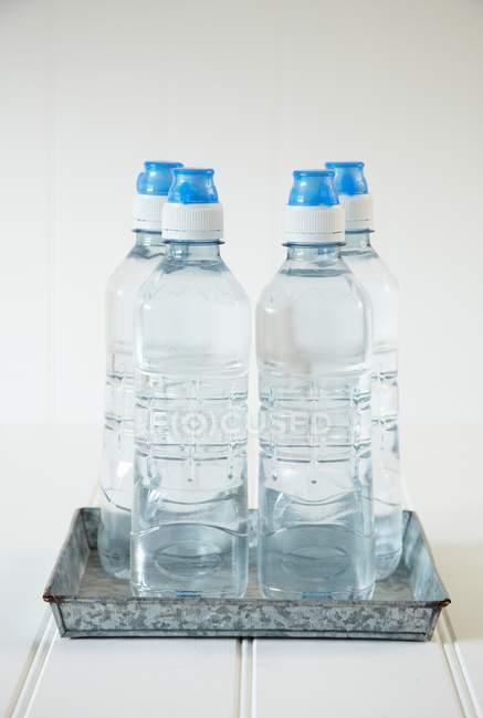 Vista ravvicinata di quattro bottiglie d'acqua su un vassoio di metallo — Foto stock