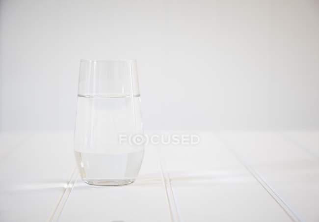 Glass of water on a white wooden table — Stock Photo