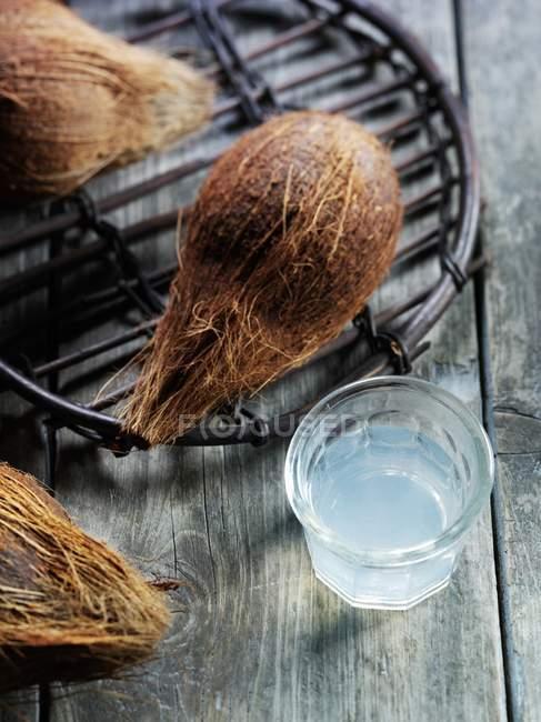 Vista de cerca de cocos y agua en vidrio - foto de stock