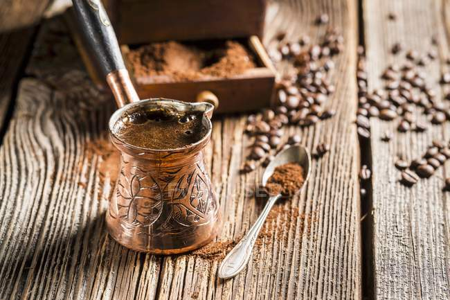 Closeup view of Turkish Mocha coffee in a copper jug with coffee powder, spoon and beans on wooden surface — Stock Photo