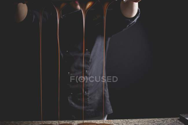 Dripping chocolate by man — Stock Photo