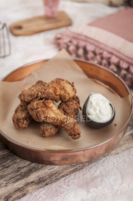 Nahaufnahme von knusprig gebratenem Hähnchen mit Sauce auf Papier — Stockfoto