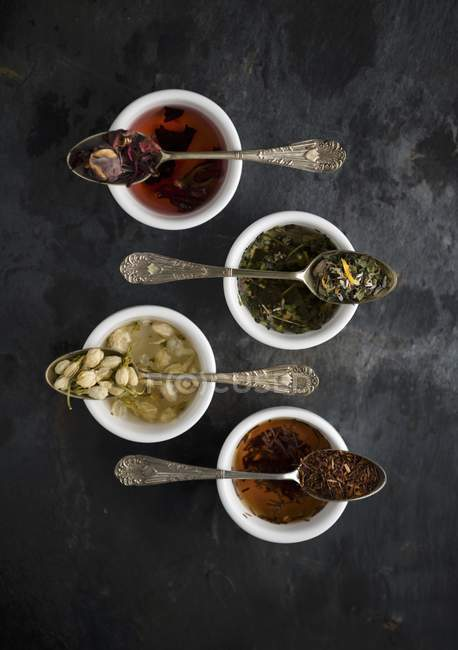 Top View Of Various Types Of Tea On Vintage Spoons Over Bowls