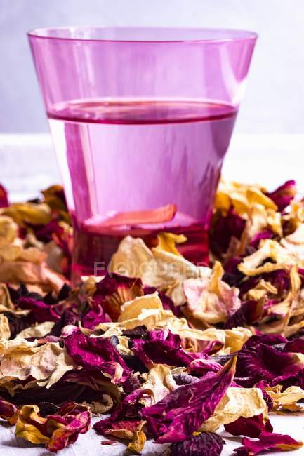 Closeup view of rose water and dried rose petals — Stock Photo
