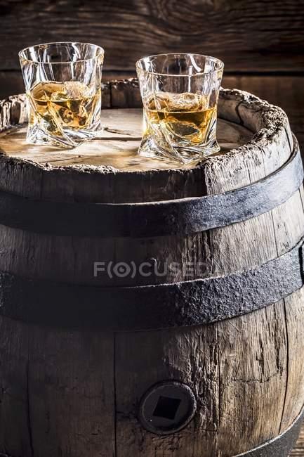 Zwei Gläser Whisky mit Eis auf alten Holzfass — Stockfoto