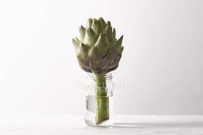 Carciofo in un bicchiere d'acqua — Foto stock