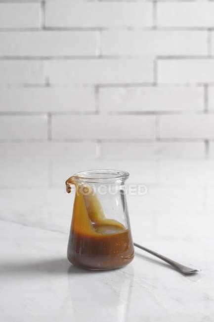 Vista de cerca de salsa de caramelo en el vaso de - foto de stock