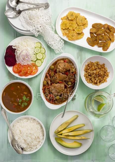 Un menú tradicional con pollo en platos y platos sobre superficie verde - foto de stock