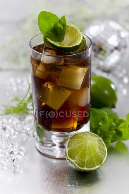Closeup view of Cuba Libre cocktail with lime, ice cubes and leaves — Stock Photo
