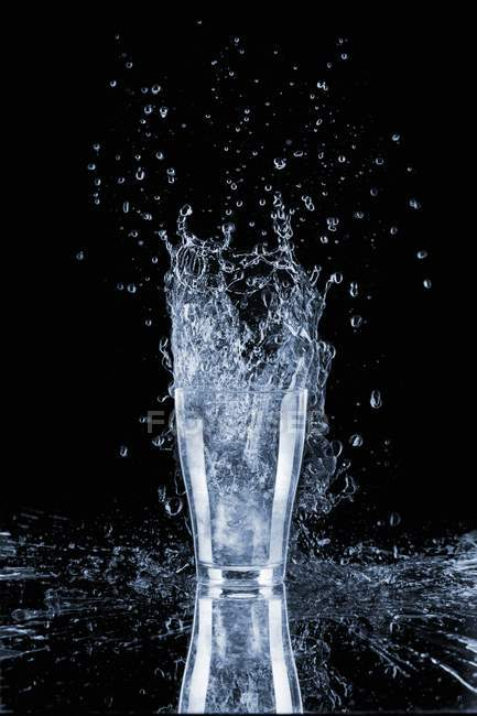 Closeup view of water glass with splash — Stock Photo