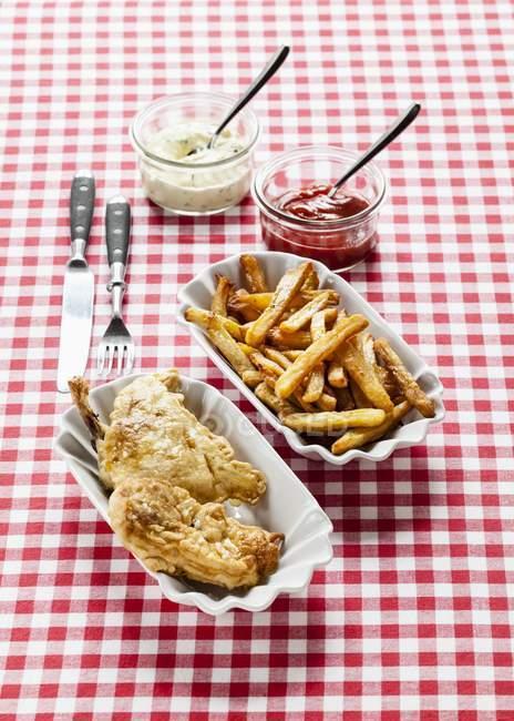 Крупным планом вид жареная курица с чипами, кетчупа и ремулад на клетчатой скатертью — стоковое фото