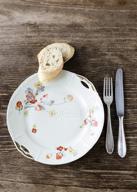 Вид зверху старим плити біла Порцеляна прикрашені квітами срібло столові прилади і дві скибочки на столі, дерев'яний багет — стокове фото