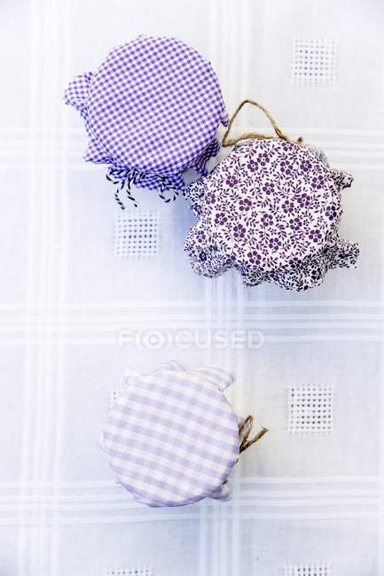 Top view of jam jars with various fabric tops — color image